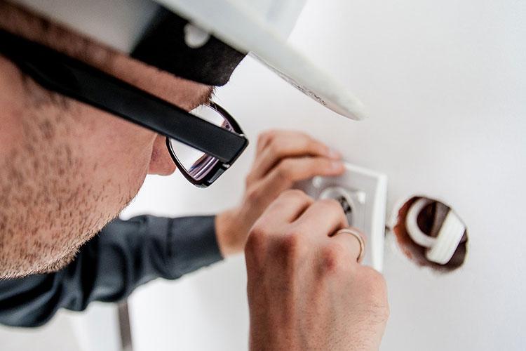 Elektrotechnik: Elektriker arbeitet an Steckdose